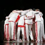 Basketball team in red and white uniforms huddling