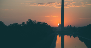 sunrise behind the us capitol and washington monument