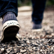 close up image of someone's feet walking on a gravel road