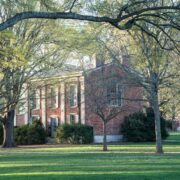 brick building on a college quad seen through trees